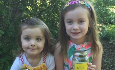 "Clara and Lily holding their ""Give"" jars full of donations for CFPA."