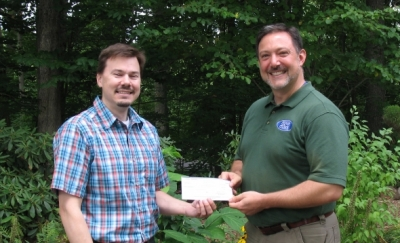 Gerry Arel of EMS presents a check to CFPA Executive Directo Eric Hammerling