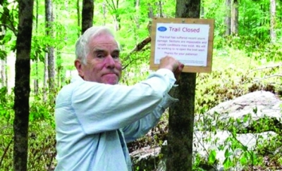 A CFPA volunteer marks a trail closure in Kettletown State Park.