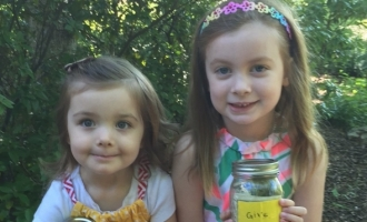 """Clara and Lily holding their """"Give"""" jars full of donations for CFPA."""